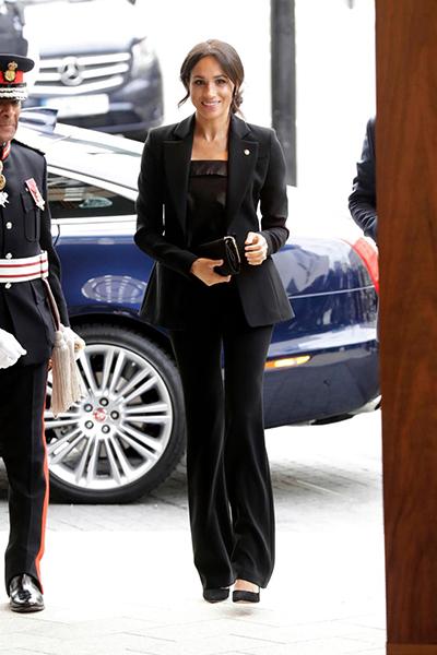 Xuất hiện tại sự kiện này, Nữ Công tước xứ Sussex lựa chọn một bộ vest màu đen, quần ống loe, làm nổi bật đôi chân thon dài. Hoàng tử Harry trông lịch lãm với bộ comple màu xanh navy, thắt cà vạt chỉnh tề.