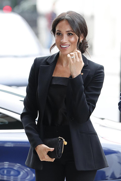 Meghan búi tóc nhẹ nhàng, sử dụng ví cầm tay cùng màu với trang phục.