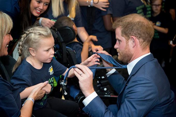 Harry thoải mái để một bé gái đùa nghịch với chiếc cà vạt của mình.