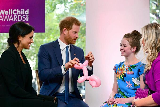Hoàng tử Harry vui vẻ làm một con chó bằng bóng cho một bé gái.
