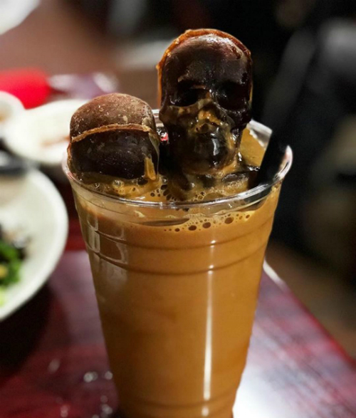 Cà phê sữa đá phiên bản Việt được cho vào cốc nhựa để mang đi dễ dàng. Phần đá bào vị cà phê phía trên thường được tạo hình đầu lâu để tạo điểm nhấn khó quên cho thực khách. Khách Mỹ khá thích thú với ly cà phê Việt Nam nên chụp ảnh check in và dành nhiều lời khen.