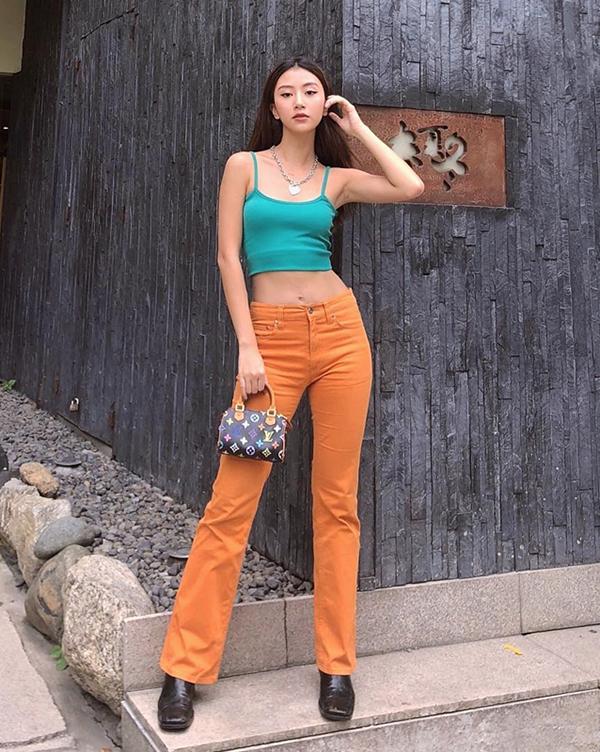 Quỳnh Anh Shyn khiến mình hút mắt hơn với cách phối hợp các tông màu nổi bật cho set đồ gồm áo hai dây, quần jeans cổ diển, túi mini của Louis Vuitton và bốt cổ thấp.