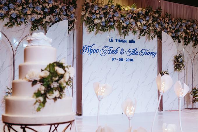 Bánh cưới của uyên ương có 4 tầng, không có hoa văn và được trang trí bởi hoa tươi.