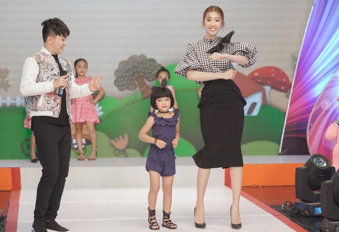 Thúy Ngân hướng dẫn một bé gái cách trình diễn sinh động khi lên sàn catwalk.