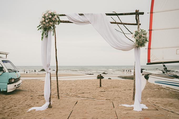 Cổng cưới được dựng đơn giản bởi cọc gỗ, có sự xuất hiện của hoa baby, hồng tươi, các mảnh vải lụa màu trắng.
