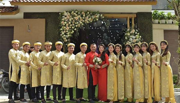Vợ chồng Trọng Hoàng mặc áo dài đỏ chụp ảnh cùng dàn trai gái bưng - nhận lễ, trong đó có trung vệ Hoàng Văn Khánh (ngoài cùng bên trái) và Phạm Xuân Mạnh (thứ 5 từ trái qua).