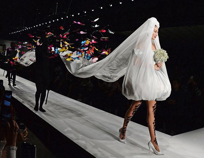 Nhà thiết kế bố trí bốn người mặc đồ đen kín mít bước sau Gigi để nâng dải voan cài đầu dài vài mét, đồng thời cầm gậy gắn đàn bướm giả sặc sỡ nhằm tạo hiệu ứng thị giác thú vị.