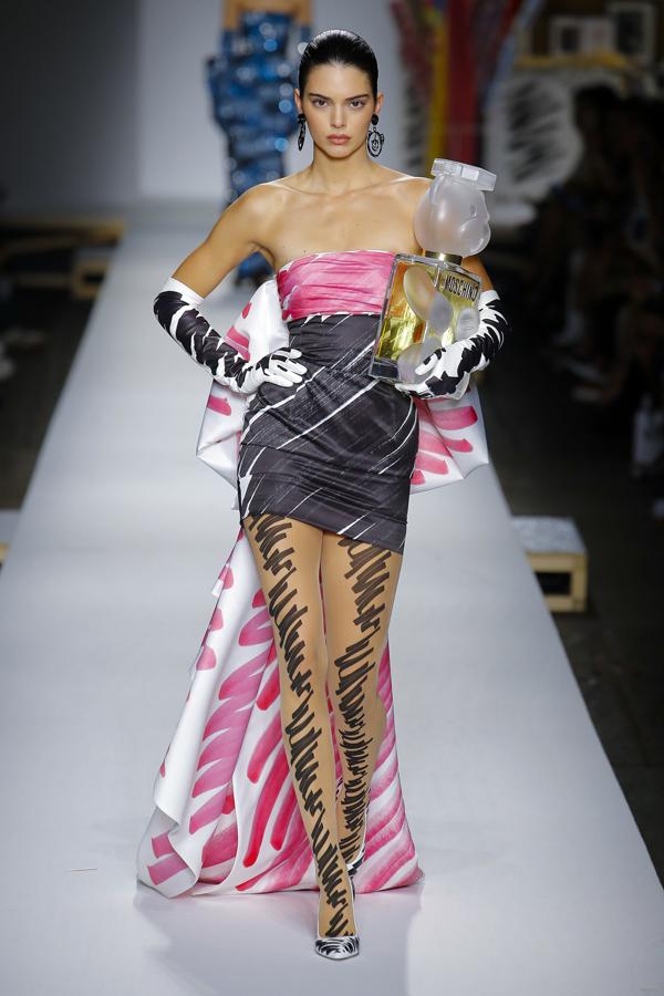 Nàng siêu mẫu thế hệ mới catwalk kiêu kỳ trong chiếc váy độc đáo, tay ôm mô hình chai nước hoa Moschino khổng lồ.