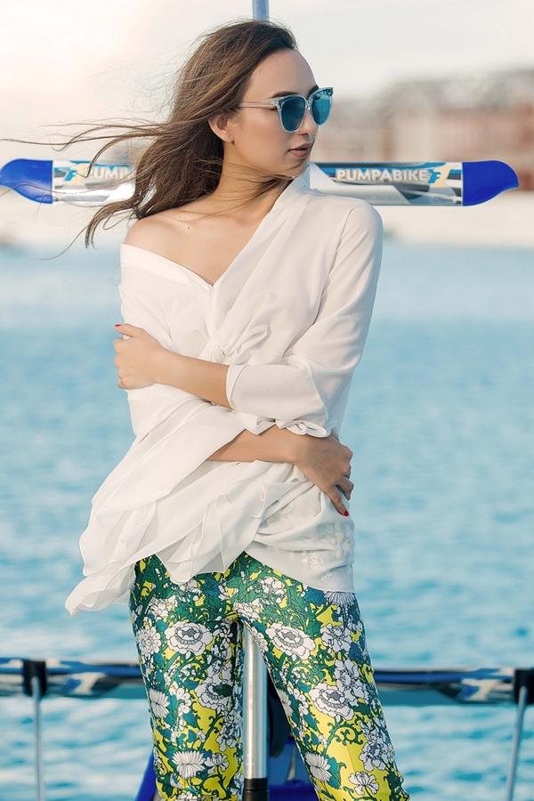 Hoa hậu Du lịch 2008 diện thiết kế quần hoa kết hợpáo sơ mi cách điệu,tôn lên vai trần trước biển.