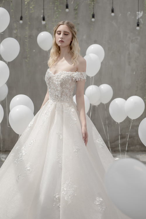 Mẫu váy trễ vai xòe bồngvới gam màu trắng tinh khôi là lựa chọn tuyệt vời cho cô có thân trên thon nhỏ, mảnh mai. Chiếc váy được định hình cứng cáp, ôm trọnkhuôn ngực và vòng eo thon nhỏ của cô dâu.