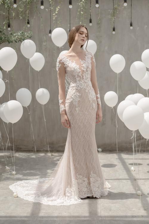 Ưu điểm của váy sheath tay dàinằm ở phần ren thêu nổi trên lớp voan mỏng, tạo nên giá trị thẩm mỹ bền vững trong làng thời trang cưới. Thiết kế uốn theo đường cong của cô dâu, vừa tôn vẻ gợi cảm quyến rũ, vừa thanh lịch.