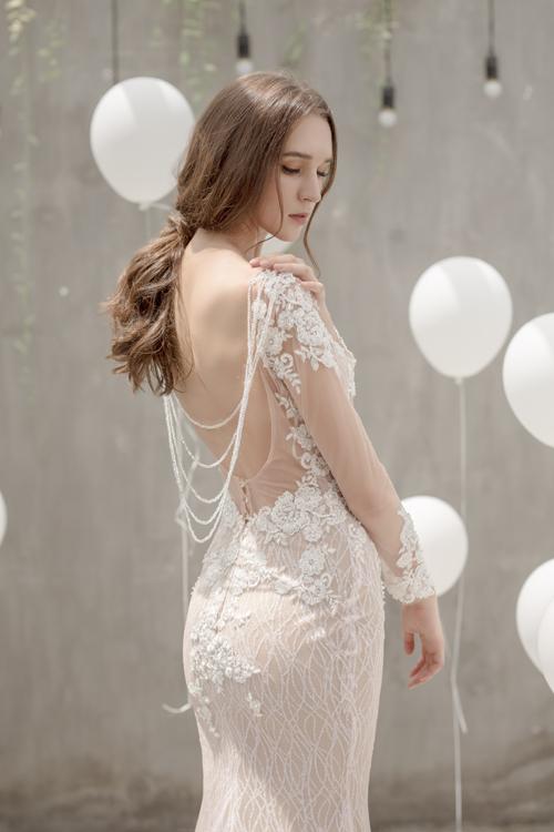 Đằng sau váy là khoảng hở lưng với đường cắt may tinh tế tôn dáng người mặc.