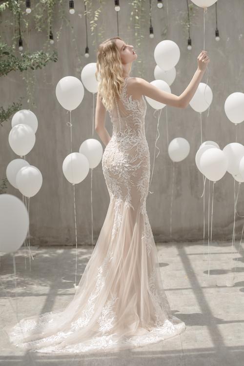 Mẫu đầm trumpet với chân váy được xẻ từ ngang đùi, độ xòe vừa phảigiúp cô dâu di chuyển thuận lợi giữa các bàn tiệc.
