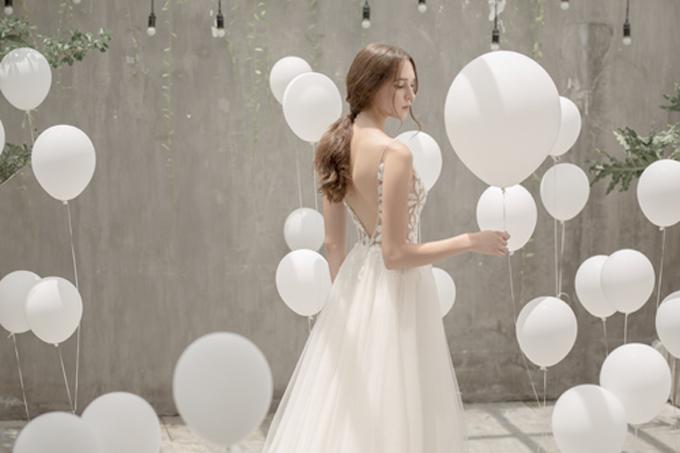 Sau khi diện váy, cô dâu có thể nhờ thợ trang điểm phủ thêm lớp kem che khuyết điểm và phấn bắt sáng để khoảng hở ở lưng thêm quyến rũ.