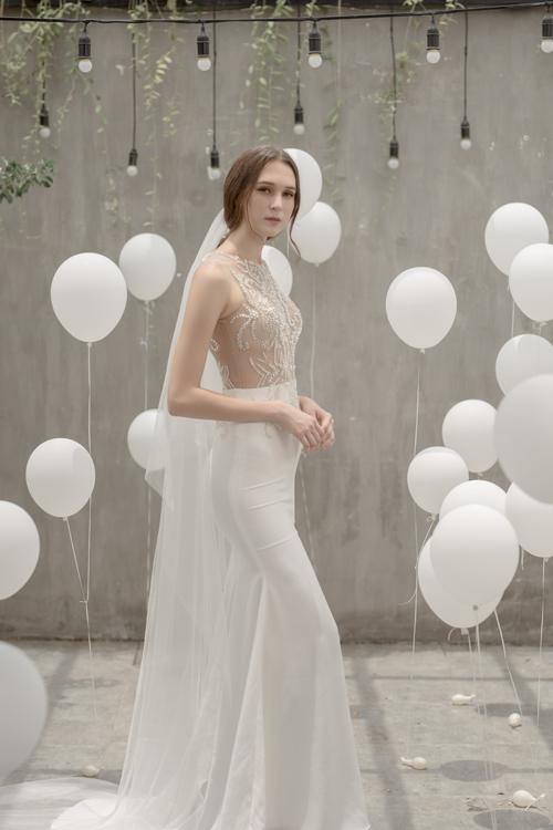 Váy cưới không tay được thêu ren nổi trên nền vải màu nude, mang đến nét gợi cảm, quyến rũ. Chân váy trơn không đính kết họa tiết giúp người mặc có vẻ đẹp thanh lịch, nhẹ nhàng.