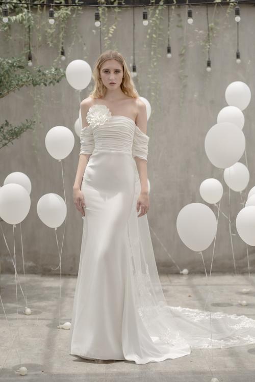 Để tạo sự thú vịcho chiếc váy dáng sheath, nhà thiết kế đã tách biệt chiếc váy thành thân trên, dưới rõ ràng. Bông hoa to bản được dùng làm điểm nhấn, giúp chiếc váy bớt đơn điệu, tẻ nhạt.