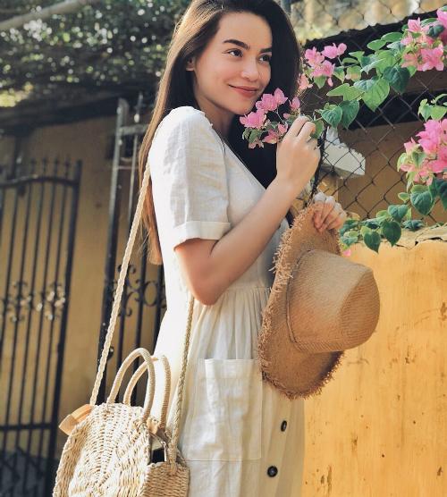 Hồ Ngọc Hà diện đầm trắng tinh khôi, e ếp bên cành hoa giấy cạnh bức tường vàng mang đặc trưng Hội An. Cô cũng có một tháng di chuyển liên tục từ trong nước đến nước ngoài, trong đó có chuyến đi Pháp và Hội An - Huế.