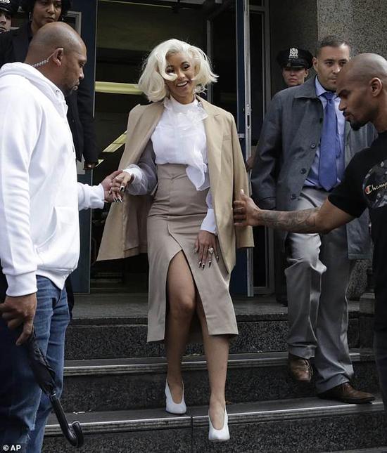 Cardi B rời đồn cảnh sát hôm 1/10. Cô mỉm cười và từ chối bình luận về vụ ẩu đả.