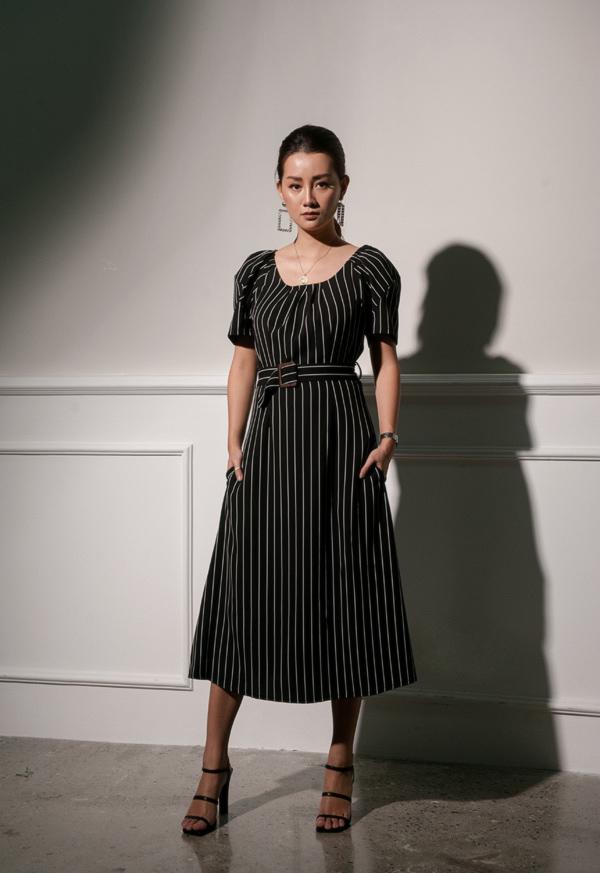 Khi diện váy midi kẻ sọc đơn giản, cô kết hợp sandal cao gót quai mảnh nhằm ăn gian chiều cao, tạo bố cục cân đối.