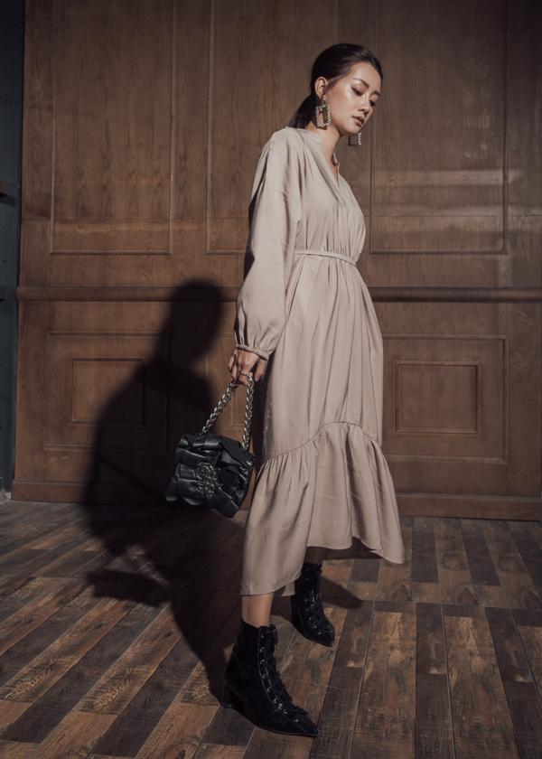 Túi xách độc đáo, bốt da cổ thấp gam đen trở thành gia vị ấn tượng cho mẫu đầm form rộng màu trung tính.