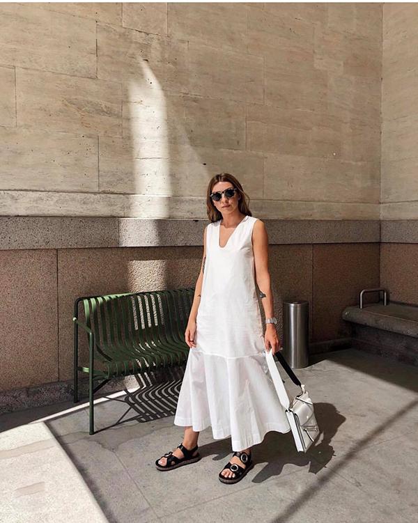 Váy tông trắng nhẹ nhàng thiết kế phom dáng rộng mang lại cảm giác thoải mái. Phối cùng bộ cánh là sandal quai da và túi tương phản sắc màu.