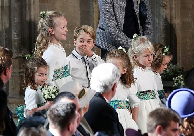 George lấy tay che miệng như để cố nín cười khi đứng cạnh chị họ Savanna Phillips bên trong nhà nguyện.