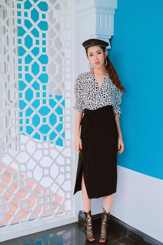 Sơ mi in họa tiết da beo đượcchọn làm điến nhấn cho set đồ trắng đengồm váy vạt quấn, bốt dây đan.