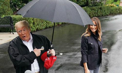 Ông Trump che ô một mình, mặc vợ ướt mưa