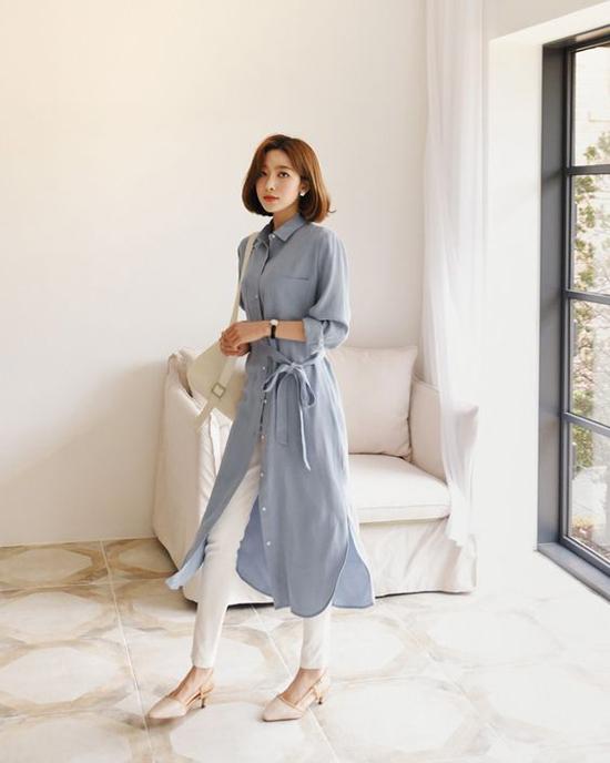 Để tránh đơn điệu khi diện sơ mi đến văn phòng, các chị em có thể chọn thêm các kiểu áo dáng dài mặc kèm đai lưng vải.