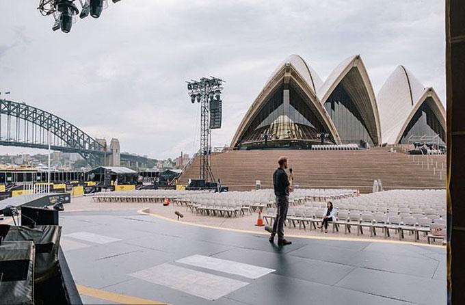 Hoàng tử Harry diễn tập trên sân khấu trong khi Meghan ngồi một mình ở hàng ghế khán giả tại Nhà hát Opera Sydney chiều 20/10. Ảnh: Điện Kensington.