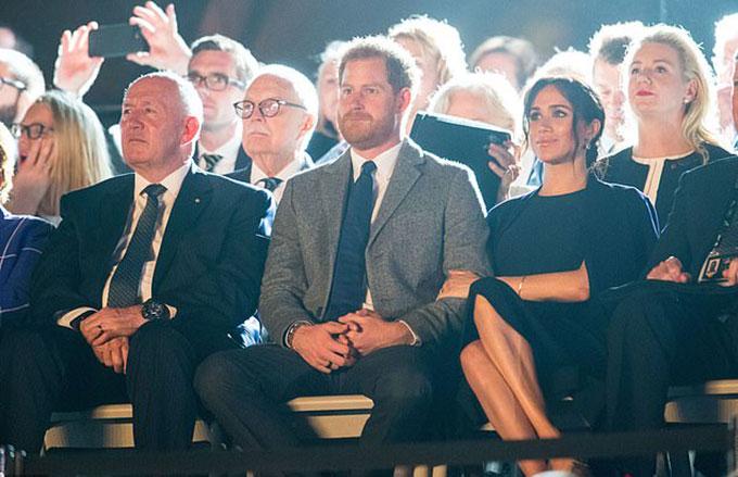 Hoàng tử Harry tỏ ra căng thẳngtrước khi phát biểu và nắm chặt tay vợ tại Nhà hát Opera Sydney tối 20/10. Ảnh: PA.