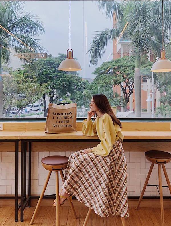 Chân váy xòe theo phong cách cổ điển được Yến Trang phối cùng áo blouse tông vàng mơ nhẹ nhàng. Phụ kiện đi kèm là sandal quai mảnh và túi tote trên chất liệu vải bố.