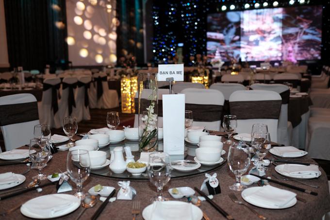 Cặp vợ chồng đặt bình hoa lan tươi cỡ nhỏđể trang trí bàn tiệc xoay, vừa làm đẹp không gian, vừa chiếm ít diện tích trên bàn tiệc. Cạnh đĩa ăn của khách mời là những món quà nho nhỏ mà cặp vợ chồng gửi đến khách mời như một lời cảm ơn.Ảnh: Kevin Đỗ