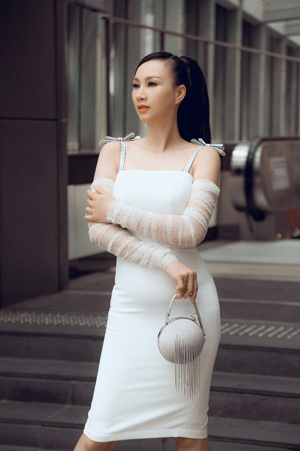 Số đo ba vòng cân đối giúp Hoa hậu Doanh nhân Paris Vũ tự tin diện thiết kế ôm dáng tông màu trắng. Mẫu váy hai dây kết hợp tay áo chất liệu voan mỏng tạo vẻ đẹpnữ tính. Phụ kiện túi tròn tô điểm phong cách thời thượng của nữ doanh nhân.