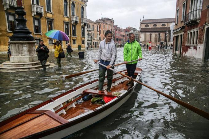 Hai người đàn ông này còn chèo thuyền gondola trên phố, khi các đường sá đều bị nước ngập nặng. Hiện người dân và các cửa hàng kinh doanh trong thành phố phải gia cố các cánh cửa bằng những tấm panel bằng gỗ hoặc kim loại nằm ngăn nước tràn vào tầng trệt, tuy nhiên, những bức ảnh được chia sẻ trên mạng xã hội cho thấy nhiều chủ quán phải sử dụng cả máy bơm nước để bảo vệ đồ đạc bên trong.