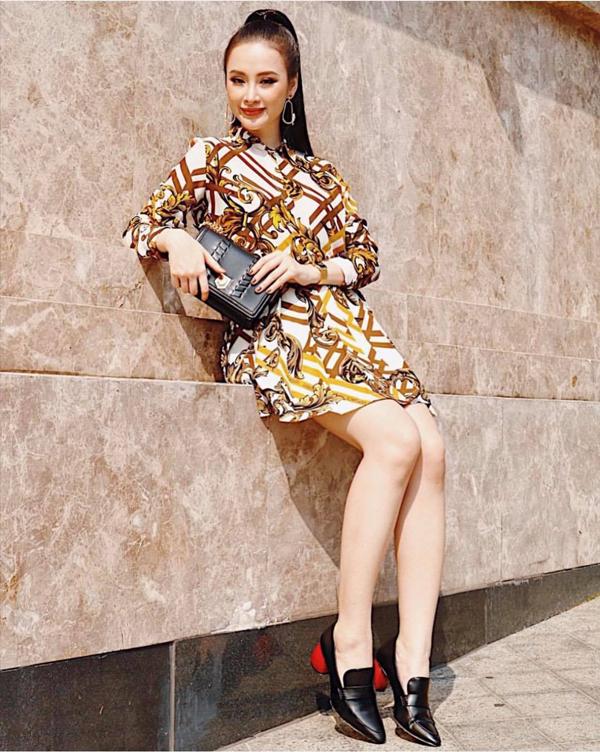 Angela Phương Trinh với hình ảnh thanh lịch và hiện đại khi chọn các phụ kiện da đen để mặc cùng bộ cánh in hoa văn bắt mắt.