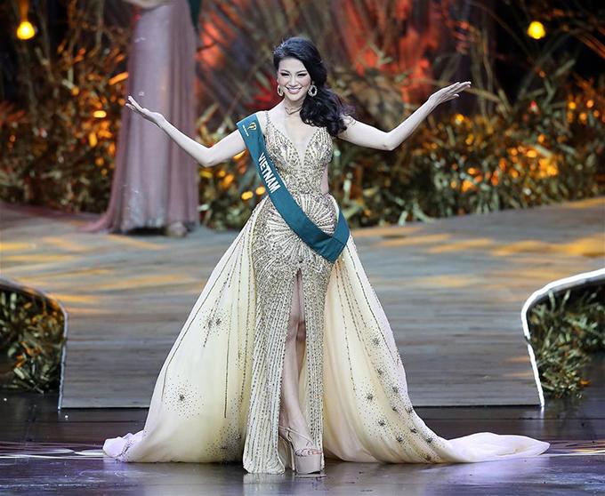 Trong phần thi Trang phục dạ hội, Phương Khánh lộng lẫy trong thiết kế của nhà thiết kế Linh San. Bộ đầm cắt xẻ khoe đường cong, đồng thời họa tiết đính đá dọc theo thân váy giống như những tia nắng mặt trời chiếu rọi. Ảnh của Xinhua.