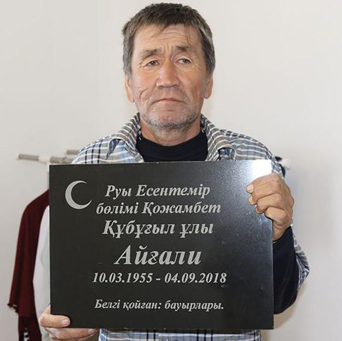 Ông Aigali Supugaliev chụp cùng bia mộ của chính mình. Ảnh: east2west news.