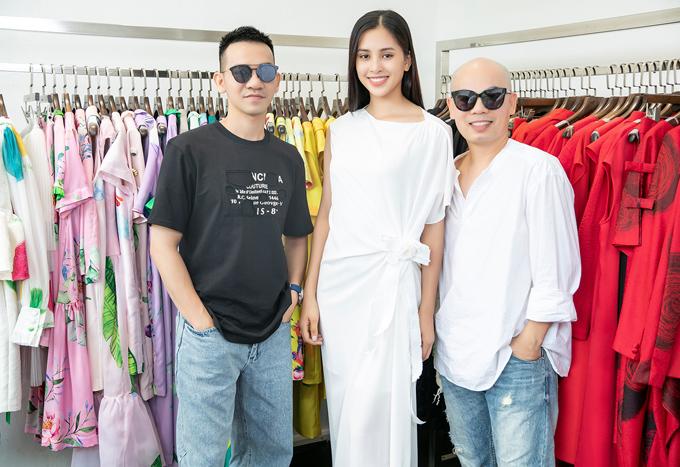 Nhà thiết kế Vũ Ngọc (áo sơmi trắng) và nhà thiết kế Son (áo thun đen) chụp ảnh cùng Hoa hậu Tiểu Vy tại showroom.