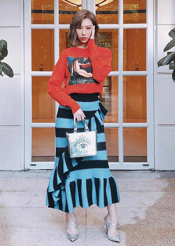 Ca sĩ Min diện nguyên set đồ của Kenzo để hòa nhịp cùng trào lưu diện màu nổi xuống phố. Cô chọn thêm phụ kiện túi xách, bốt ánh kim tạo điểm nhấn cho tổng thể.