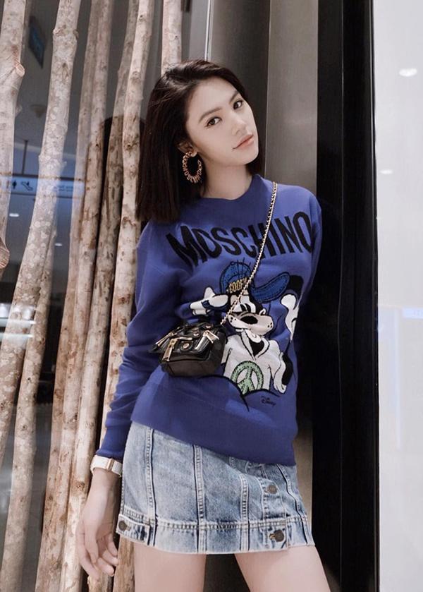 Jolie Nguyễn kết hợp áo hoodie họa tiết họa hìnhvới chân váy denim cài nút. Phụ kiện đi kèm làtúi Moschino nhỏ xinh, làm tăng nét trẻ trung.