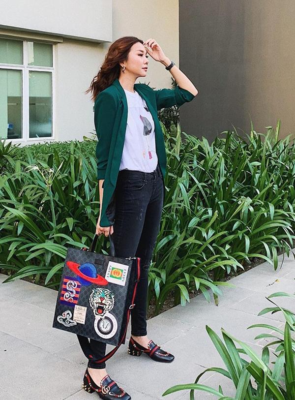 Khi diện đồ theo phong cách menswear, Thanh Hằng chọn thêm túi tote đính đầy sticker của Gucci để tăng sức hút cho tổng thể.