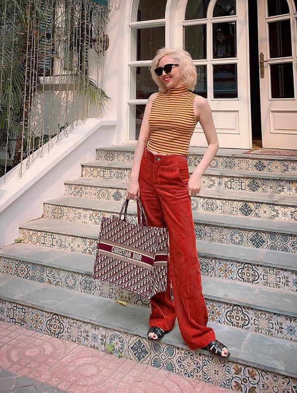 Quần nhung đỏ cảm, áo thun tông vàng đan xen kẻ sọc được Tóc Tiên kết hợp cùng nhau để thể hiện sự sành điệu cùng xu hướng màu sắc thu đông. Cô chọn thêmtúi tote book của Dior, có giá gần 60 triệu đồng để phối đồ.