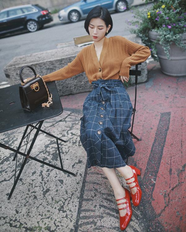Váy midi thiết kế trên các chất liệu vải kẻ sọc ca rô sử dụng cùng các kiểu áo len, áo nỉ, sweater là công thức lên đồ hài hòa cho quý cô công ở mùa thu đông.
