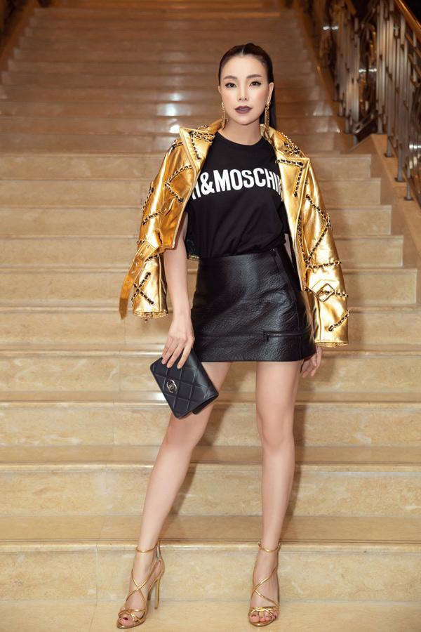 Trà Ngọc Hằng chọn áo jacket ánh kim để phối cùng áo thun in logo và chân váy da siêu ngắn.