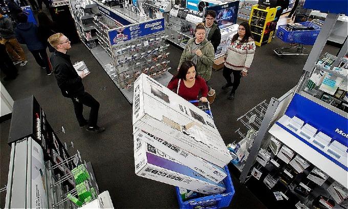 Một phụ nữ tậuba chiếc TV giảm giá trong dịp mở cửa sớm của Thứ Sáu Đen Tối. Ảnh: AP.