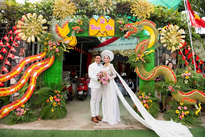 Cổng hoa nhà chồng Đặng Thu Thảo trang trí ấn tượng với hình long, phụng kết từ lá dừa và các loại trái cây đặc trưng ở miền Tây Nam Bộ.