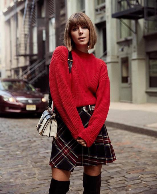Đột nhiên một ngày, bạn muốn trẻ trung hơn tuổi thì có thể thử diện chân váy ngắn họa tiết kẻ sọc ca rô cùng áo len đỏ tươi và bốt cao cổ.