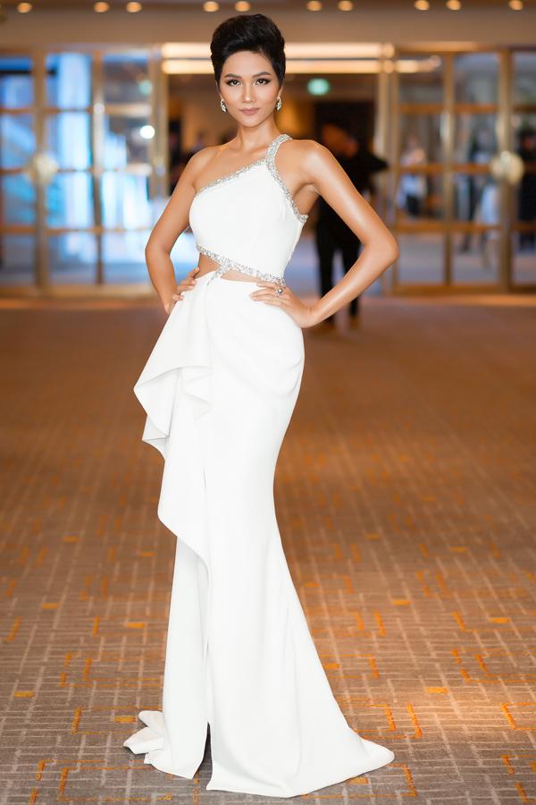 HHen Niê thử một trang phục gam trắng lệch vai, cut-out ở eo. Do làn da của Hoa hậu ngăm đen nên nhà thiết kế chọn cho cô các màu nổi như vàng, đỏ, xanh lá hoặc những gam trung tính trắng, đen. Da ngăm mà mặc trang phục màu nhẹ nhàng nhìn tổng thể sẽ bị tái, cũ kỹ, thiếu sức sống, NTK Linh San giải thích.