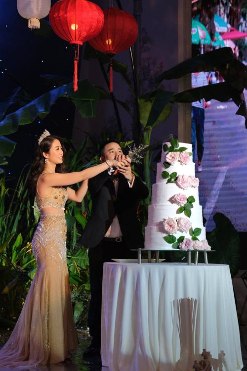 Cặp vợ chồng chọn bánh cưới 5 tầng được tô điểm bởi hoa tường vy.
